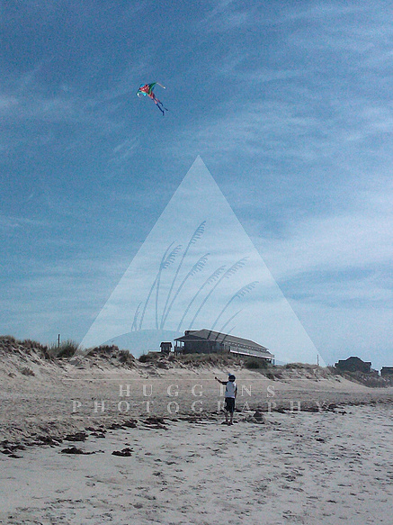 A boy flies a kite at the beach