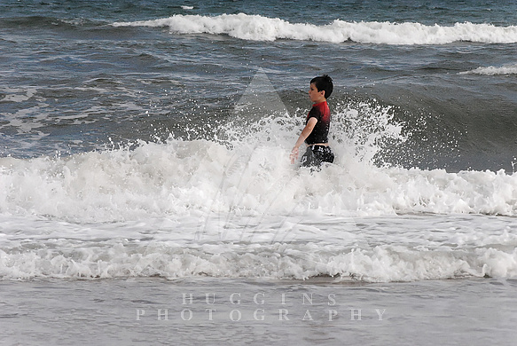 A boy wades in Hatteras waves.