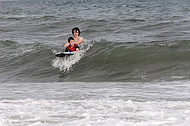 Big brother instructs sibling on surfing.
