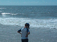 A boy stands in the surf.