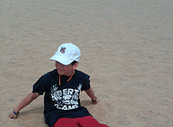 A boy relaxes on a sand dune