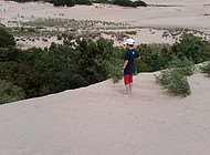 A boy looks out from a dune